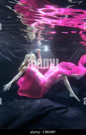 Caucasian woman in dress swimming under water