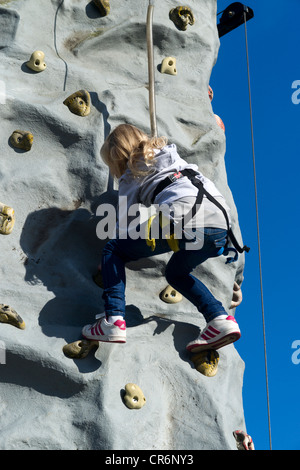 A young girl Climbing on a climbing wall at Birkenhead Festival of Transport 2011. - Stock Photo
