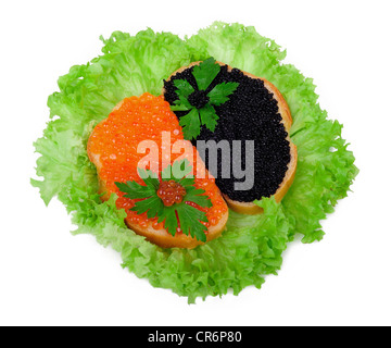 Sandwiches with red and black caviar on lettuce leaves - Stock Photo