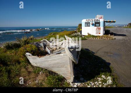 Wooden dinghy, and Nins Bin lobster caravan, Kaikoura Coast, Marlborough, South Island, New Zealand - Stock Photo