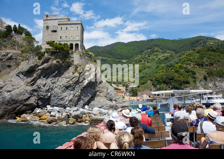 Boat with tourists in front of the Castello Monte Rosso watchtower, , Cinque Terre, La Spezia Province, Parco Nazionale - Stock Photo