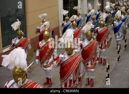 Men dressed as Roman legionaries parade through the street during an Easter Holy Week procession in Puente Genil - Stock Photo