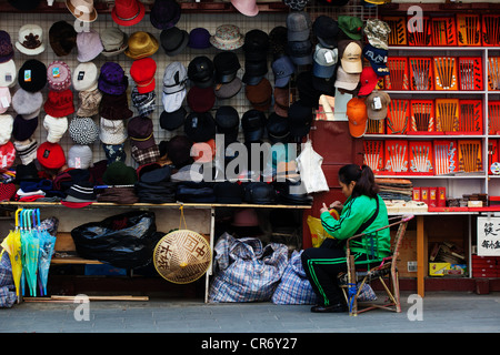 Street stall of China Shanghai selling hats and other chinese culture items. - Stock Photo