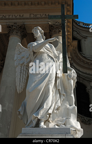 Sculpture of an angel with a cross in front of Karlskirche, St. Charles Church, Roman Baroque, completed 1737, Karlsplatz - Stock Photo