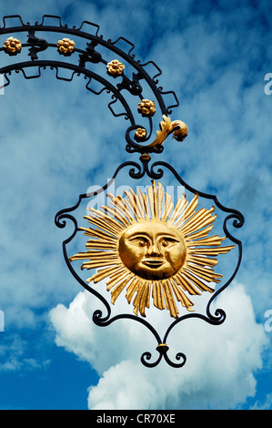 Hanging sign of 'Hotel Gasthof Sonne', restaurant and hotel, against a cloudy sky, Hauptstrasse, Gengenbach, Baden - Stock Photo