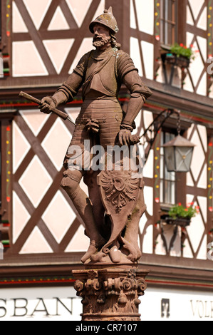 Sculpture of a knight with shield and coat of arms on Roehrbrunnen fountain, 1582, old half-timbered house at back - Stock Photo