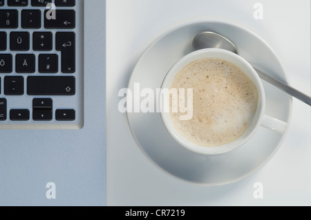 Laptop and cup of coffee on white background - Stock Photo