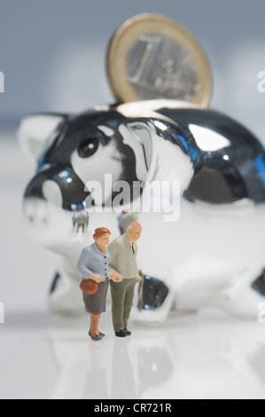 Senior couple figurines besides piggy bank with euro coin - Stock Photo