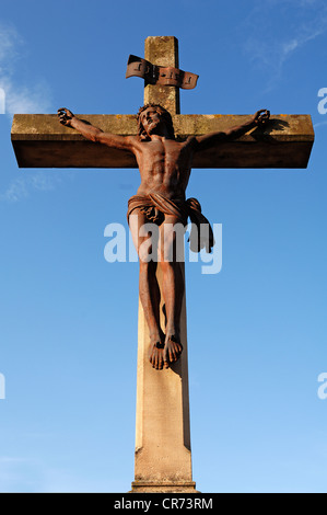 Rusted cast-iron statue of Christ on a stone cross, 19th Century, against a blue sky in the cemetery of Guebwiller - Stock Photo
