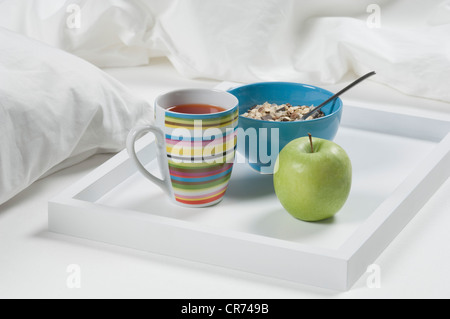 Tray of tea, apple and muesli on bed for breakfast, close up - Stock Photo
