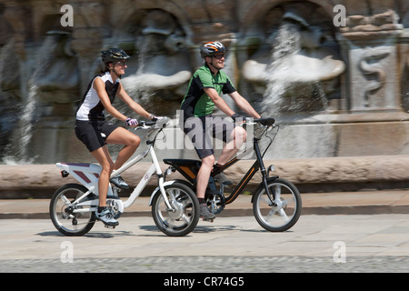 Germany, Bavaria, Munich, Man and woman riding electric bicycle - Stock Photo