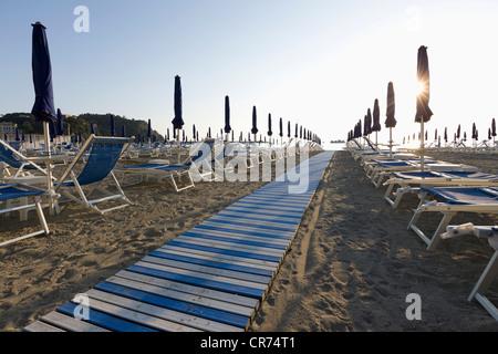 Italy, Liguria, Sestri Levante, Row of outdoor chairs and sunshade on beach - Stock Photo