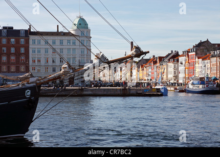 View at the Nyhavn canal across the harbour in the port of Copenhagen through the rig and  bowsprit of an old sailing - Stock Photo