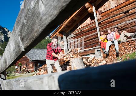 Austria, Salzburg County, Friends looking at man chopping wood near alpine hut - Stock Photo