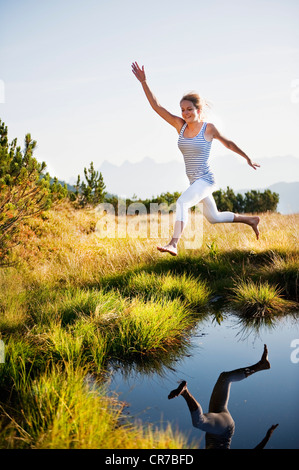 Austria, Salzburg County, Young woman jumping over mountain lake - Stock Photo