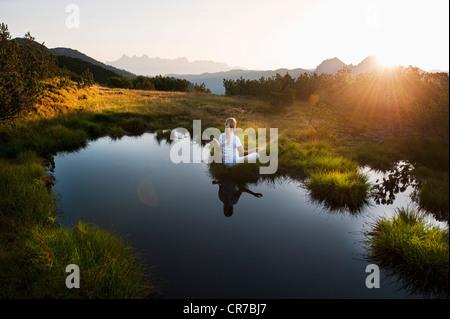 Austria, Salzburg County, Young woman sitting near mountain lake and doing meditation - Stock Photo