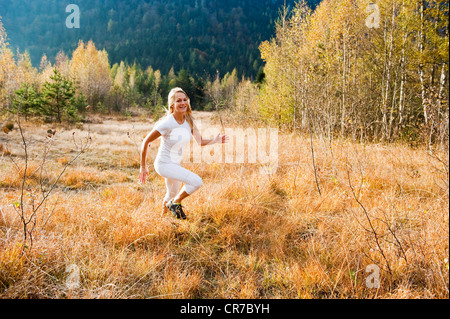 Austria, Salzburg, Young woman running in autumn - Stock Photo