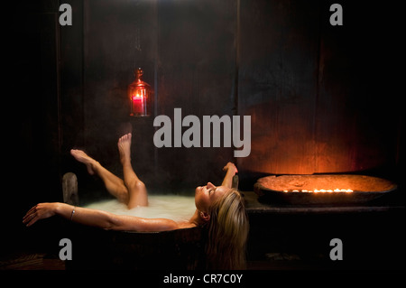 Austria, Salzburg County, Young woman taking bath in wooden tub - Stock Photo