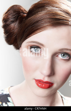 Vintage style portrait of model with red hair tied in a bun - Stock Photo