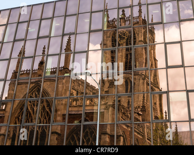 Reflection of Holy Trinity Church Hull in glazed front of an office building - Stock Photo