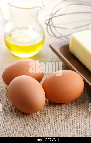 Eggs with oil butter and whisk - Stock Photo