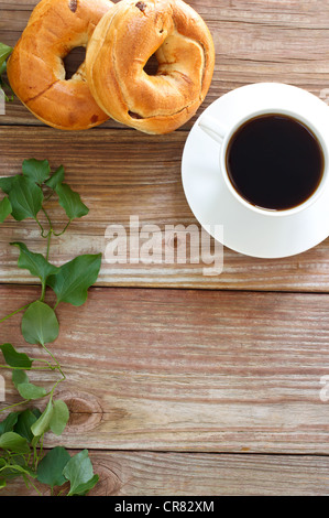 fresh cup of hot coffee with bagels on rustic wood slaps with copyspace - Stock Photo