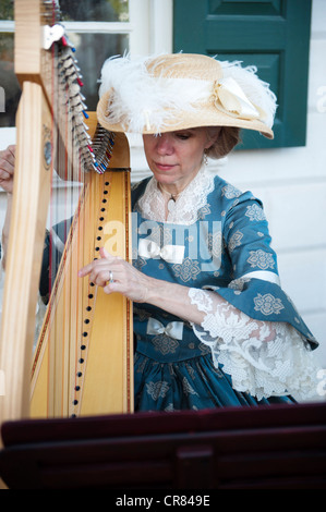 Woman playing a harp dressed in vintage 19rh century clothing at Mount Vernon, George Washington's home. - Stock Photo