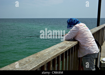 Female angler leaning on wide wooden railing Gulf Shores State Park Alabama sport fishing pier hazy overcast - Stock Photo