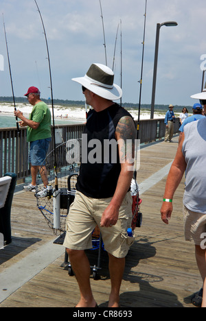Angler towing fishing tackle cart Gulf Shores State Park Alabama sport angling pier boardwalk - Stock Photo