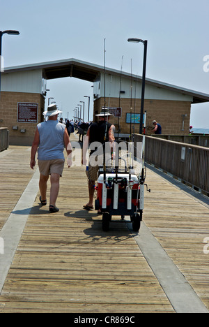 Anglers towing fishing tackle cart Gulf Shores State Park Alabama sport angling pier boardwalk - Stock Photo