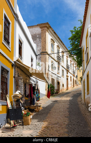 Local shop on a narrow cobbled street leading up to the Castle in the Old Town, Silves, Algarve, Portugal - Stock Photo