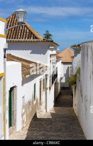 Narrow cobbled street in the Old Town, Tavira, Algarve, Portugal - Stock Photo
