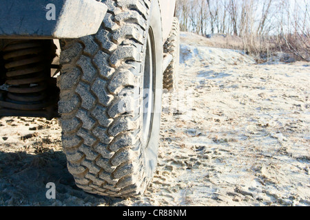 Off-road tire. The aggressive tread pattern. Installed on the Niva SUV. - Stock Photo