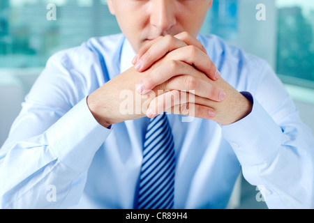 Close-up of businessman keeping fingers crossed by his face - Stock Photo