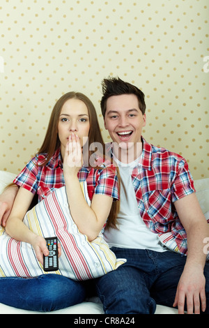 Portrait of young couple during watching TV - Stock Photo