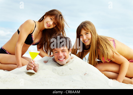 Two girls in bikini and happy guy with cocktail having fun on sandy beach - Stock Photo