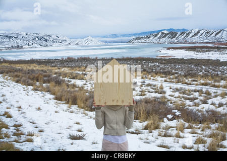 Woman in scenic landscape with wooden shape of a house - Stock Photo