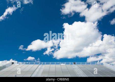 Blue sky and clouds above empty stadium seats - Stock Photo