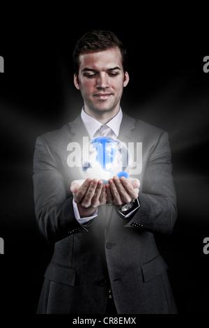 Man holding holographic globe - Stock Photo