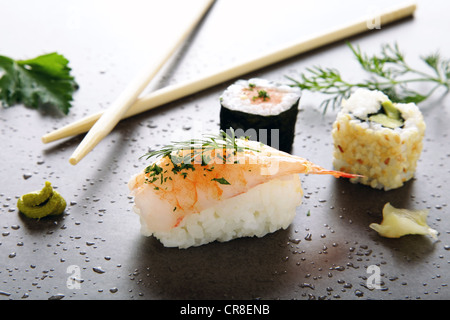 Assorted sushi with ginger and wasabi on a stone surface - Stock Photo