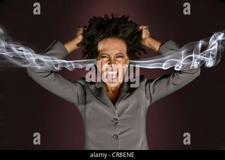 Frustrated woman with smoke coming from ears - Stock Photo