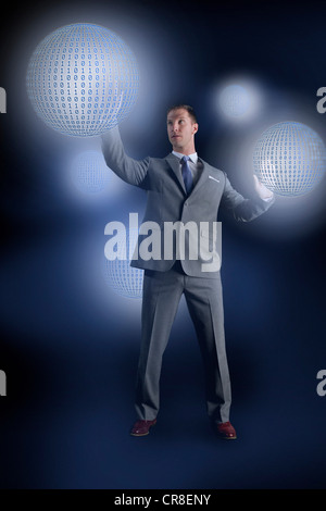 Businessman interacting with holographic binary globes - Stock Photo