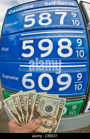 Hand holding dollar bills at gas station in Death Valley National Park, California, USA - Stock Photo