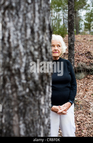 Portrait of senior woman in forest, hands clasped - Stock Photo