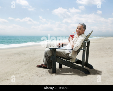 Mature man relaxing in chair on beach - Stock Photo
