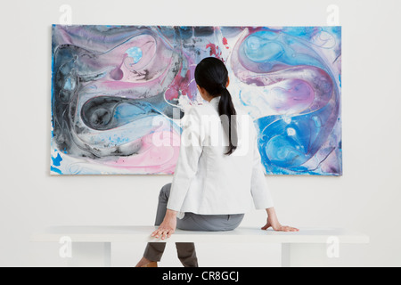 Young woman looking at oil painting in gallery - Stock Photo