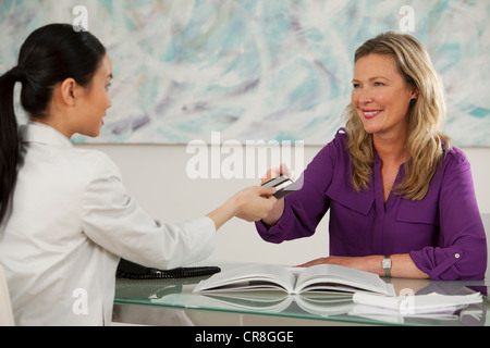 Art dealer taking credit card from young woman at desk in gallery - Stock Photo