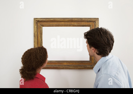 Young couple looking at blank image in picture frame - Stock Photo