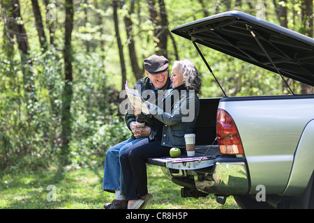 Senior couple reading map while sitting on car trunk in forest - Stock Photo