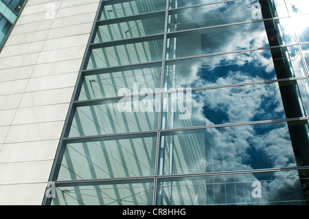 Cloudy blue sky reflected in office windows - Stock Photo